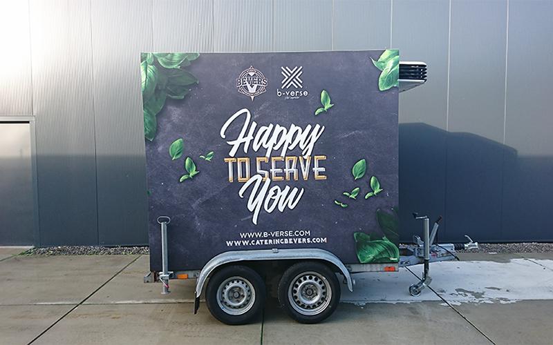 Een aanhangwagen van Bevers is bestickerd met reclame.