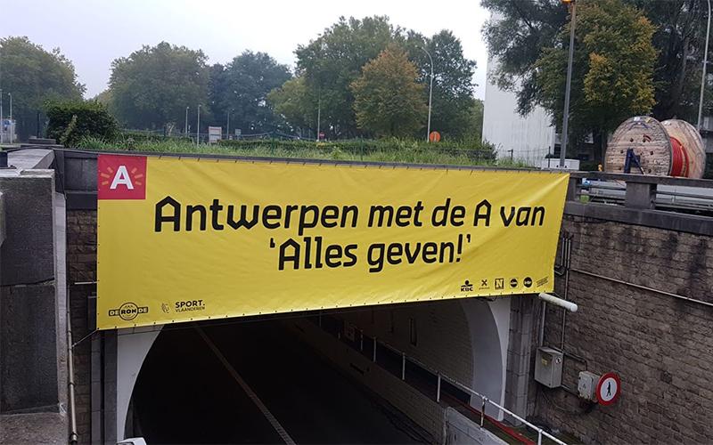 Een banner van stad Antwerpen hangt boven een brug. De banner is van het materiaal frontlit.