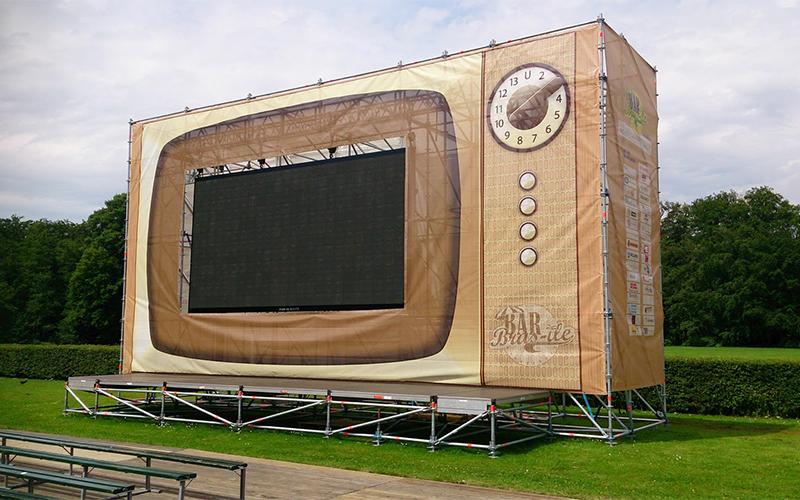 Een stelling is bekleed met doeken met de print van een radio op het festival Brasile.