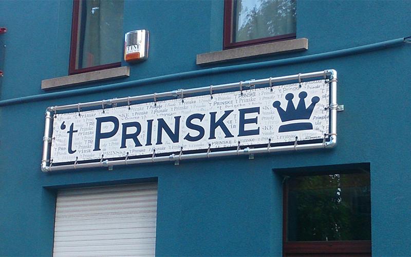 Een banner met de naam 't Prinske hangt op de gevel van een gebouw.
