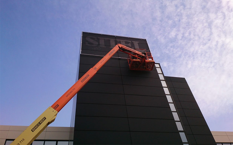 Een medewerker van All Signs staat op een kraan om een spandoekframe aan een toren te hangen.