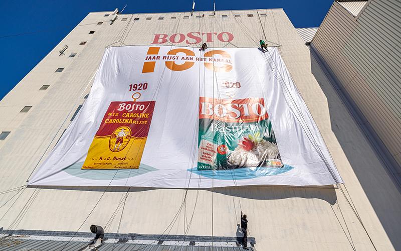 Plaatsers hangen aan de gevel van de Bostotoren om de banner op te hangen.
