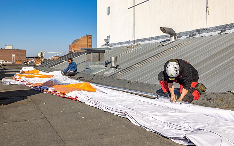 Plaatsers bevestigen touwen aan het spandoek voor de Bostotoren