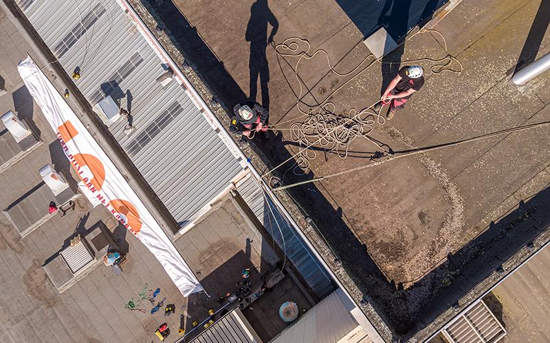 Plaatsers staan op het dak van de Bostotoren om de banner naar boven te hijsen.