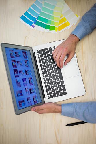 Een grafisch vormgever is bezig op zijn laptop.