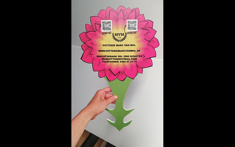 Plantenprikker in de vorm van een bloem. Er staan contactgegevens op van de Potter Marc Van Mol.