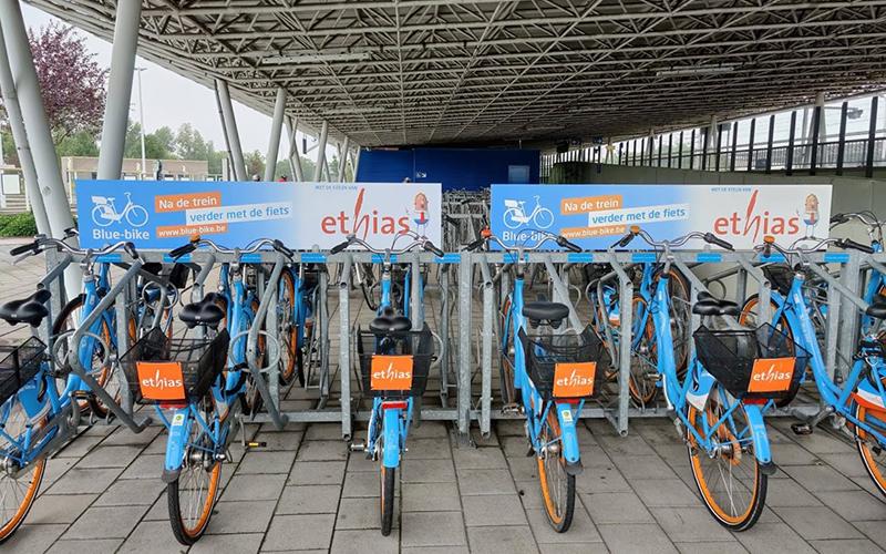 Reclamepanelen van Blue Bike die bij de fietsen staan.