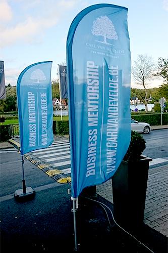 Beachvlaggen die voor de ingang van een event van Carl Vandevelde staan.