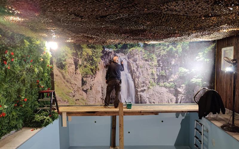 Een medewerker van All Signs kleeft behang.