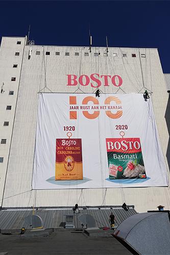 Medewerkers hangen aan een touw om een doek van Bosto aan een gobouw te hangen.