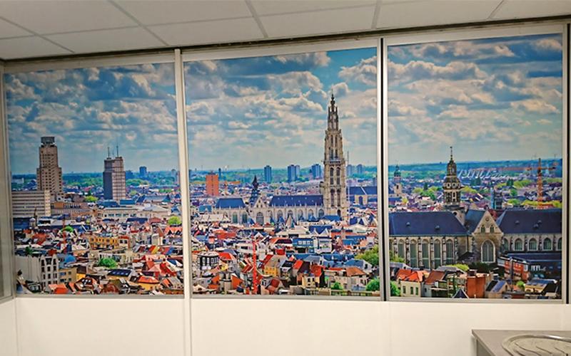 Sticker van een foto van stad Antwerpen die aan de binnenkant van een kantoorruimte is gekleefd.